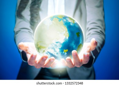 Business woman standing with open palm holding the earth with both hands over blue background. Earth day concept