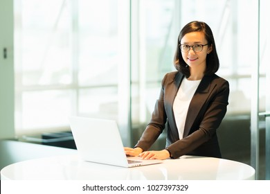 Business Woman standing working with laptop working on desk in modern office