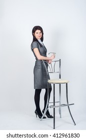Business woman stands leaning on a chair in the Studio. Photo in full growth