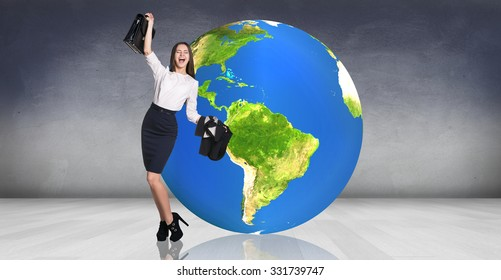 Business woman stands near big earth ball in the gray room. Elements of this image furnished by NASA
