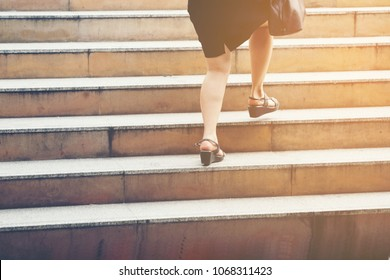 business woman stepping up the stairs,Businessmen rushed to rush go work to keep up.Employees who come to work late.