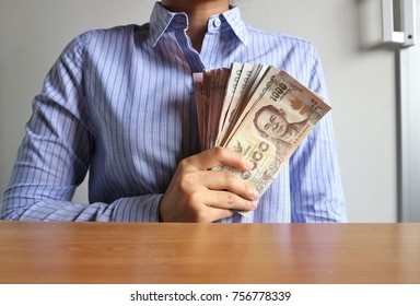 Business woman in striped shirt hold pile of Thai Baht money on wood table in white room background