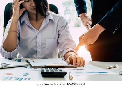 Business woman struggling and her boss pointing at watch to meet challenging deadlines.