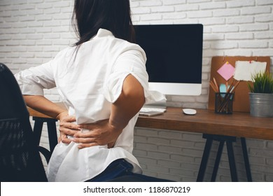 Business woman suffering from back pain in office home