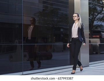 Business woman in suit with glasses and tablet in her hand walking on the street in business quarter