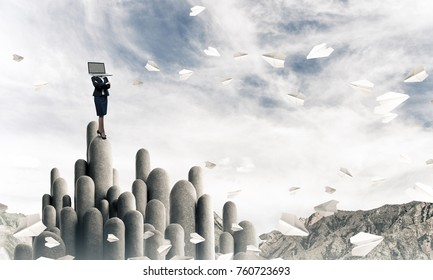 Business woman in suit with laptop instead of head keeping arms crossed while standing on the top of stone column with beautiful skyscape on background. 3D rendering.