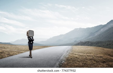 Business woman in suit with an old TV instead of head keeping arms crossed while standing on the road with beautiful landscape on background.