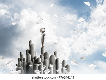 Business woman in suit with an old TV instead of head keeping arms crossed while standing on the top of stone columns among flying paper planes with beautiful landscape on background. 3D rendering.