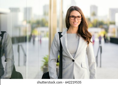 Business woman in suit portrait during travel for company meeting outdoor brunette with glasses