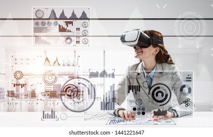 Business woman in suit using virtual reality goggles while sitting inside bright office building. Concept of modern technologies for business needs.