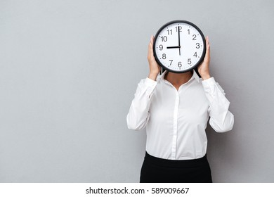 Business woman in suit which hiding behind the clock. Isolated gray background