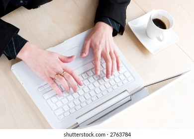 A business woman in a suit working on her laptop with half a cup of coffee