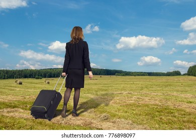 Business woman with suitcase is the summer field, dreaming about the rest.