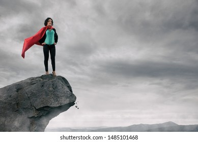 Business woman as a super hero on the peak of a mountain