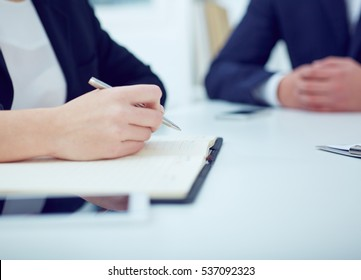 Business woman taking notes at office workplace with colleague on the background. Business job offer, financial success, certified public accountant concept.