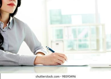 Business woman taking notes at seminar