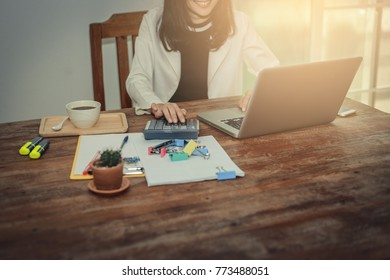 Business woman taking business notes  using laptop computer pen calculator paper clip paper work on wood table  .