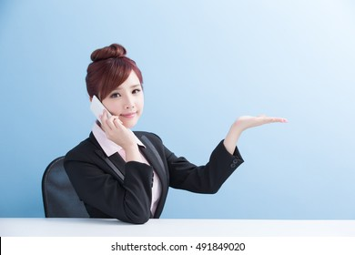 business woman talk on phone and show something with isolated on blue background, asian