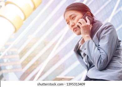 Business woman is talking on the phone. She is tired and homesick when she aboard.