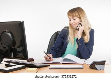 Business woman talking on the phone and writes in the book office