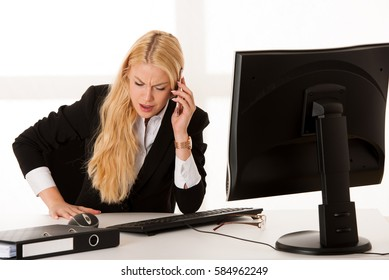 Business woman talking on phone in office.