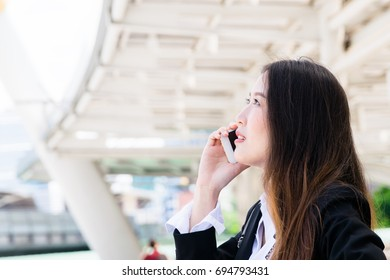 Business woman talking on the phone on her way to the office : business outside concept