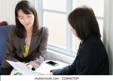 business woman team using smart phone and meeting with colleagues to discuss financial results