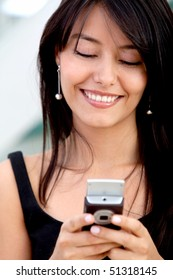 Business woman texting on her mobile phone and smiling