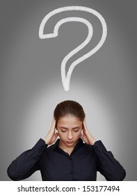 Business woman thinking hard with question sign above head on grey background