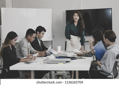 Business woman throwing papers with fury because tired of meeting at meeting room in office.