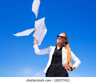 Business woman throwing stack of papers in the air