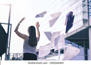 Business woman throwing work papers in the air. Stress from workload. Person going home or leaving for vacation. Employee got fired. Job or project done. Difficult workday over. Outside of office.