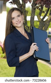 Business Woman Traveler in Smart Blue Suit Jacket Holding Laptop Computer