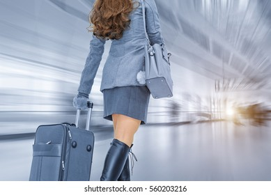 Business woman traveling and holding suitcase in the airport