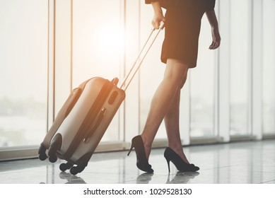 Business woman traveling with trolley. Women's legs, close-up