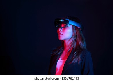 Business woman try vr glasses hololens in the dark room. Portrait of young asian girl experience ar communication. Future technology concept.