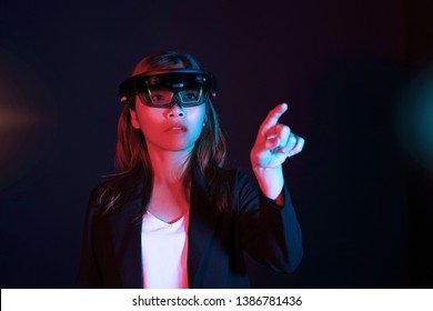 Business woman try vr glasses hololens in the dark room. Portrait of young asian girl experience ar communication. Future technology concept
