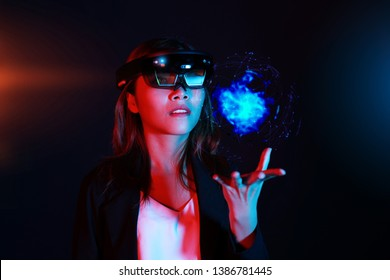 Business woman try vr glasses hololens in the dark room. Young asian girl experience ar with glow earth globe on hand. Future technology concept
