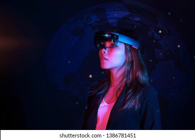 Business woman try vr glasses hololens in the dark room. Colorful portrait of young asian girl wearing virtual reality headset.