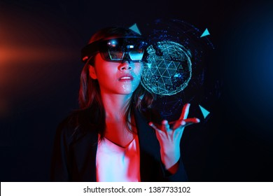 Business woman try vr glasses hololens 1 in the dark room. Young asian girl experience ar with glow energy ball on hand. Future technology concept