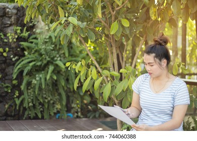 Business woman with t-shirt look at cell phone and paper for business target, business technology outdoor, idea concept