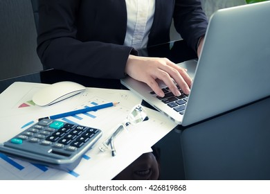 Business woman typing on a laptop in office.