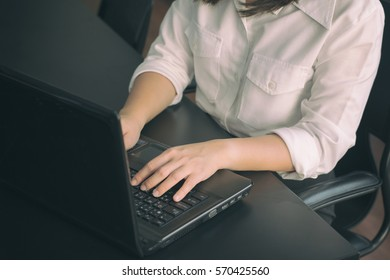 Business woman typing on laptop keyboard with vintage filter background