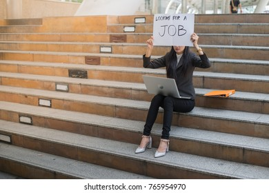 business woman unemployed from company sitting on the staircase and holding poster with text is looking for job, concept of unemployment problem