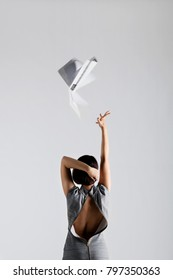 business woman with unzipped dress throwing work papers in the air