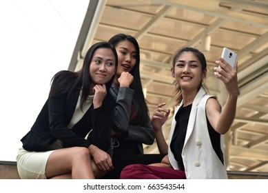 Business woman use her smartphone for selfie with her friend in modern city background