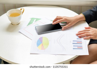 business woman use smart phone analyze reported data