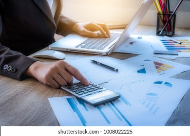 Business woman uses a calculator for calculate the company's performance figures, graphs the monthly graphs for the meeting. teamwork workplace strategy Concept