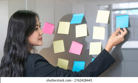 business woman uses paper post stick on glass and standing front of glass war in room with nature trees background.