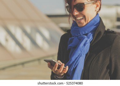 Business woman uses smart phone outdoors